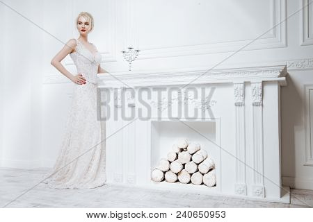 Full length portrait of a beautiful young woman in evening or wedding white dress. Luxurious white apartments.