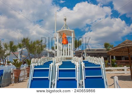 Rows Of Blue Folded Chaise Lounges And A Rescue Tower With A Rescue Jelly. Summer Vacation, Safety O