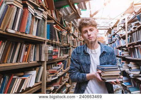 Student Stands In An Atmospheric Library With Books In His Hands And Looks At The Camera. Portrait O