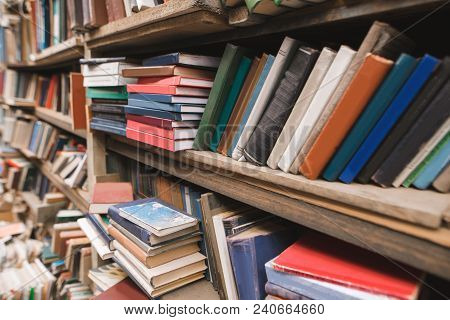 Shelves With Books In The Old Library. Book Shelves Background. Old Books On Bibliotekke Shelves.