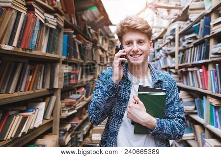 Portrait Of A Happy Young Man Standing With Books In His Hands In A Public Library And Talking On Th