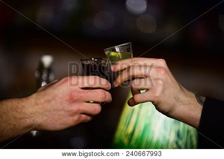 Male Hands Cheers With Alcohol On Blurred Bar Background. Friends Drink Shot Or Liqueur In Bar. Cele