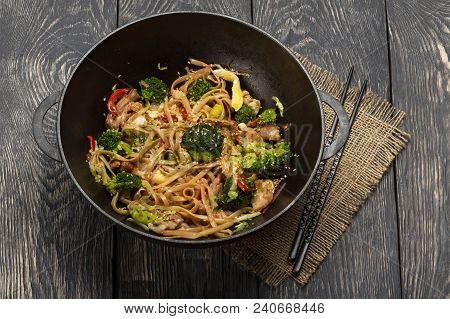 In Pan-wok Noodles With Meat And Broccoli, Chopsticks On An Old Wooden Table