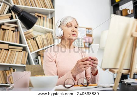 Foreign Language. Low Angle Of Focused Mature Woman Listening To Audio And Staring At Screen