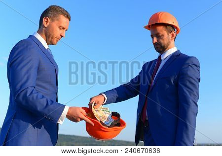Bribery And Business Bargain Concept. Architects With Serious Faces In Formal Wear And Helmets Share