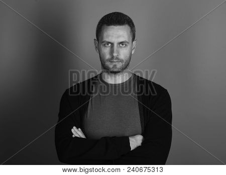 Man With Bristle Or Beard Holds Arms Crossed. Macho With Confident Face Expression On Grey Backgroun