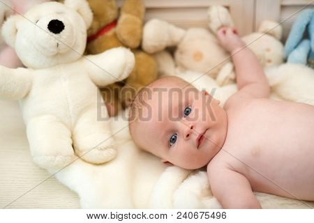 Baby Boy And His White Teddy Bear. Childhood And Curiosity Concept. Baby Lying On White Duvet. Infan