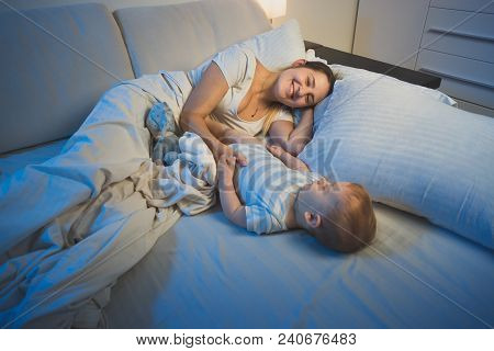 Happy Smiling Mother Lying In Bed With Her 9 Months Old Baby Son At Night