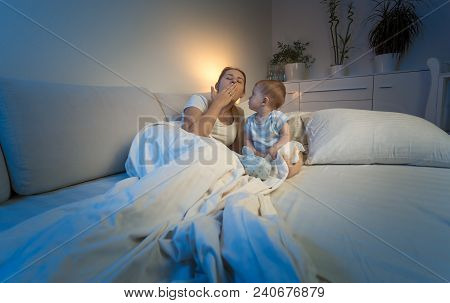 Tired Mother Lying In Bed With Her Baby Boy And Yawning