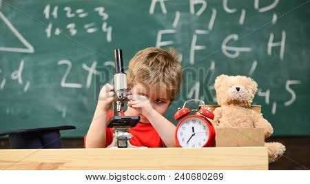 Kid Boy Looks Into Microscope In Classroom, Chalkboard On Background. Child On Busy Face Near Clock