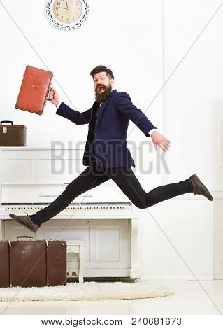 Long Awaited Vacation Concept. Man With Beard And Mustache In Suit Carries Luggage, Luxury White Int