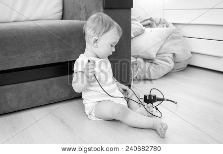 Black And White Photo Of Little Baby Boy Sitting Alone At Room And Pulling Electric Cables And Wires