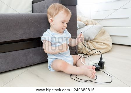 Unattended Little Baby Boy Playing With Electric Socket And Cables At Home