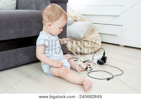 9 Months Old Baby Playing And Pulling Electric Cables And Wires. Children In Danger