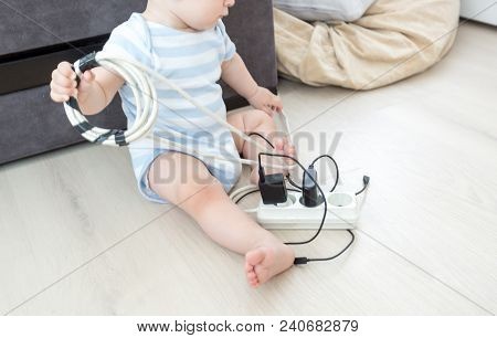 Closeup Photo Of Unatteded Baby Boy Playing With Electric Cables Under High Voltage At Home