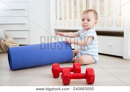 Portrait Of 9 Months Old Baby Boy Playing With Dumbbells And Fitness Mat At Home