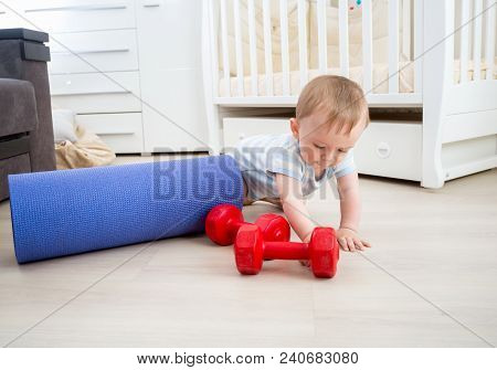 Baby Boy Playing With Fitness Equipment On Floor At Home