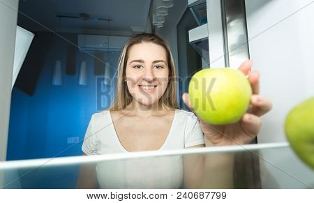 Smiling Young Woman In Pajamas Taking Fresh Green Apple Out Of Refrigerator At Night