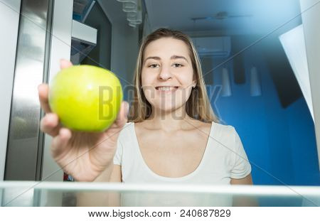Hungry Woman Taking Fresh Green Apple From Refrigarot Shelf At Night