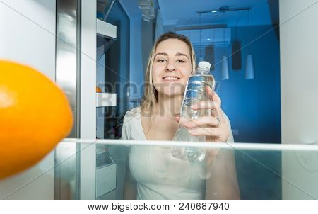 Young Woman Taking Bottle Of Water From The Refrigerator At Night