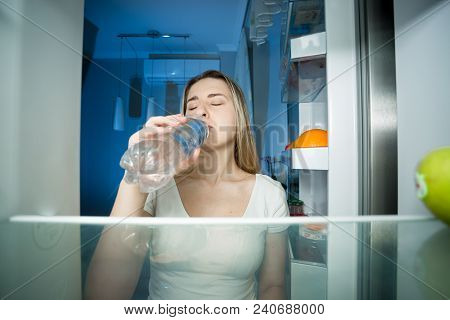 Young Woman Standing At Open Refrigerator And Drinking Water. Concept Of Dieting And Loosing Weight