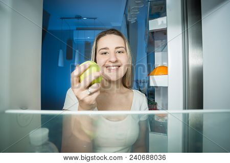 Portrait From Inside Of Refrigerator Of Smiling Woman Holding Fresh Green Apple