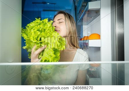 Young Hungry Woman Looking Inside Of Refrigerator And Taking Fresh Healthy Lettuce
