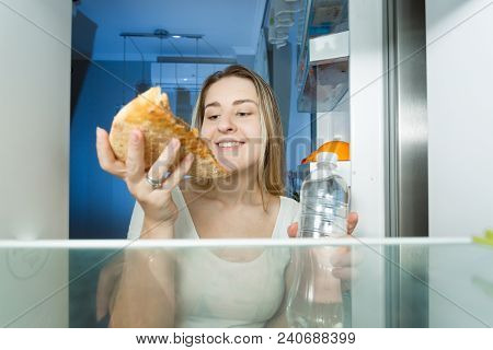 Portrait Of Woman Felling Hungry At Night Choosing Between High-calorie Pizza And Bottle Of Water