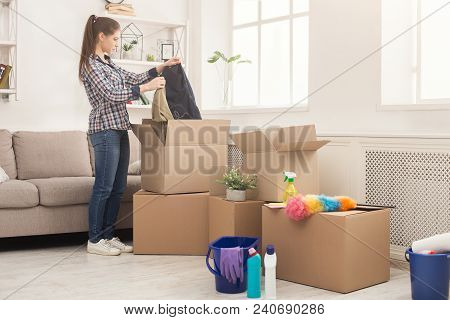 New Home Cleaning. Young Woman Tidying Up And Unpacking Boxes After Moving To New Apartment. Girl Wi