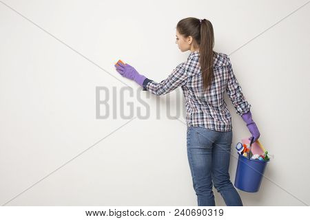 Woman Wiping White Wall From Dust With Dry Rag, Back View. Cleaning Service Or Regular Clean Up Conc