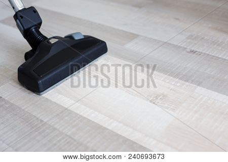 Modern Vacuum Cleaner Over Wooden Parquet Floor Background