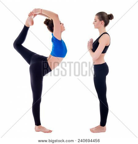 Side View Of Two Young Slim Women Doing Yoga Isolated On White Background