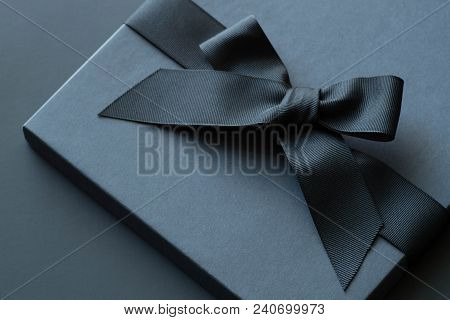 Black Gift Box On A Dark Contrasted Background, Decorated With A Textured Bow And Feathers, Creating