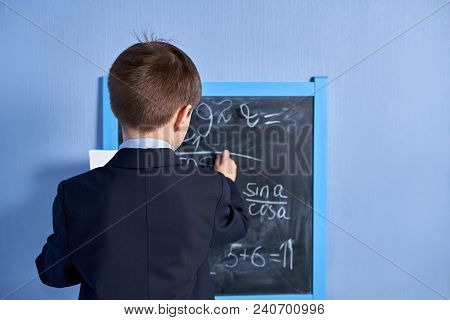 Caucasian Schoolboy Doing Task In A Classroom. Back View.