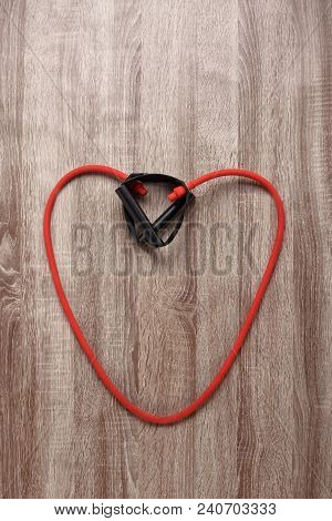 Red Heart Shaped Expander On Wooden Background