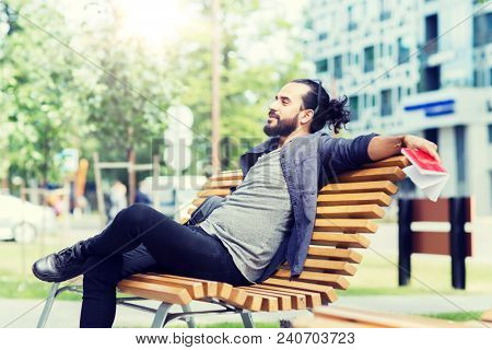 lifestyle, creativity, freelance, inspiration and people concept - creative man with notebook and bag sitting on city street bench