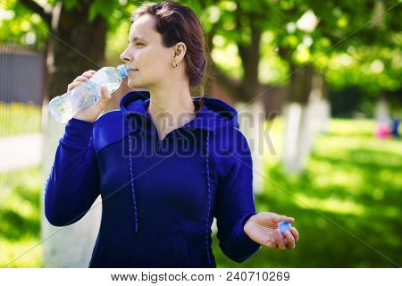 Brunette Girl Drinks Drinking Water From Bottle In Green Summer Park. Healthy Lifestyle. Drinking Cl