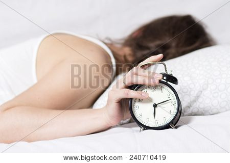 Girl Is Sleeping On Bed In Bedroom And Turns Off Alarm Clock. Woman Does Not Want To Wake Up In Earl