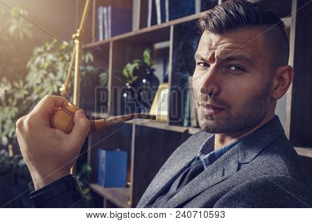 young fashionable rich man with bristle and stylish hairdo sits in an chair and smokes pipe in luxurious room. brutal look of young pensive man in luxurious apartment. Handsome man in suit smokes poster