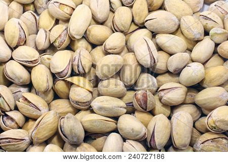 Big Set Of Salted Pistachios On The Table. Pistachios Nuts Macro Close Up Background Photo.