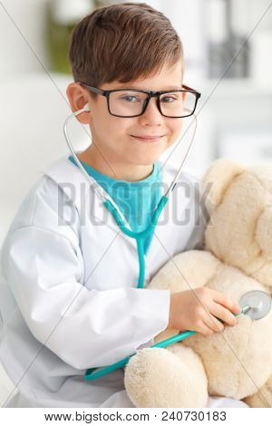 Cute little boy dressed as doctor playing with toy bear in hospital