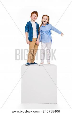 Cute Happy Children Standing On White Cube And Smiling At Camera Isolated On White