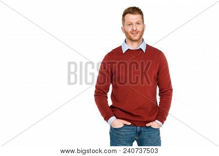 Portrait Of Handsome Redhead Man Standing With Hands On Pockets And Smiling At Camera Isolated On Wh