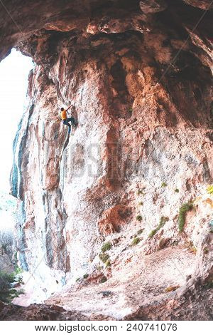 A Man Climbs The Rock. Rock In The Form Of An Arch. Cave. Fitness Outdoors. Extreme Sports. The Athl