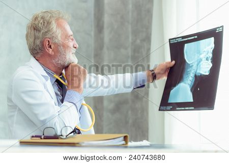 Portrait Of Male Senior Doctor Is Examining X-ray Film In Examination Room., Healthcare And Occupati