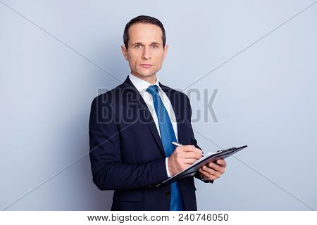 Portrait Of Focused Clever Intelligent Concentrated Representative With Pencil And Clipboard Writing
