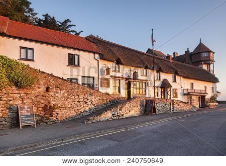 19 June 2017:  Lynmouth Devon, England, Uk - The Old Cottages Of Mars Hill, With The Rising Sun Refl