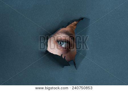 Eye Looking Through Paper. Spy Eye Watching Through A Hole. Eye Looking Through Hole In Black Paper.