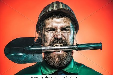 Mining And Construction Concept - Man With Angry Face In Protective Helmet Holds Shovel In Teeth. Be