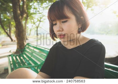 Young Asian Woman Sitting Alone On The Public Bench In The Park Surrounded With Nature And Warm Sunl